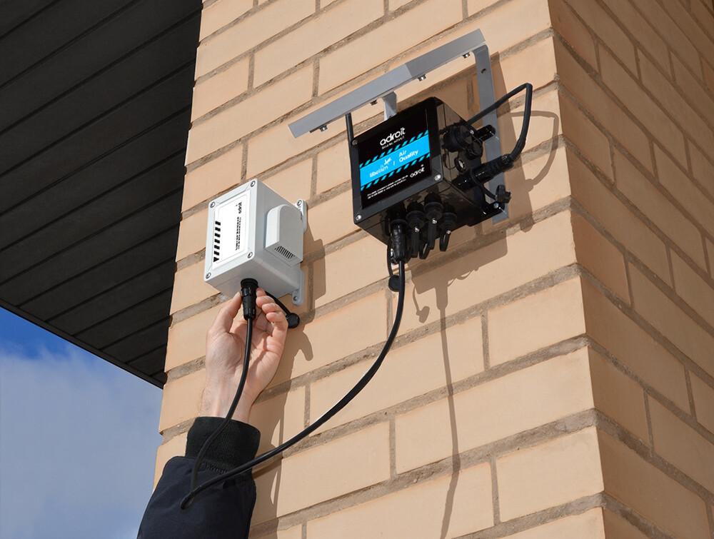 Air dust sensor mounted on brick building